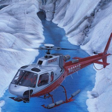 https://truealaskantours.com/wp-content/uploads/2014/05/Helicopter-over-melt-stream-on-glacier-377x377-1-377x377.jpg